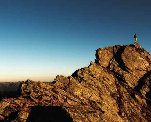 man standing on top of rock at daytime